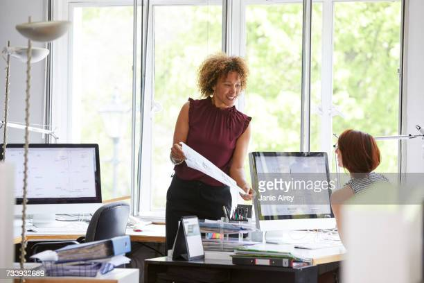 Female designers looking at blueprint in office