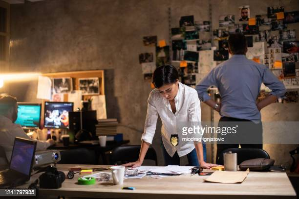female detective working late at night at office - police station stock pictures, royalty-free photos & images