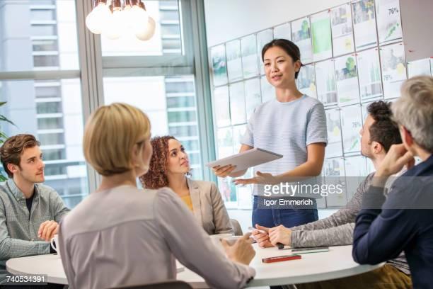 Female digital designer explaining ideas to team at conference table