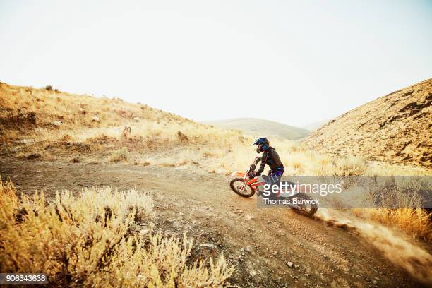 Female dirt bike rider climbing hill during desert ride on summer evening