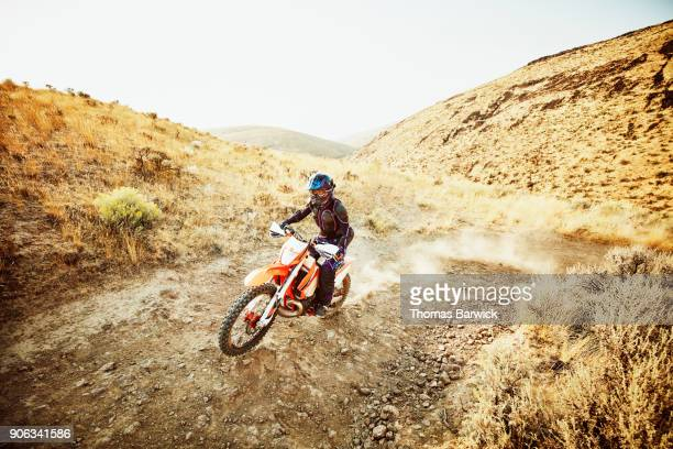 Female dirt bike rider climbing hill during desert ride