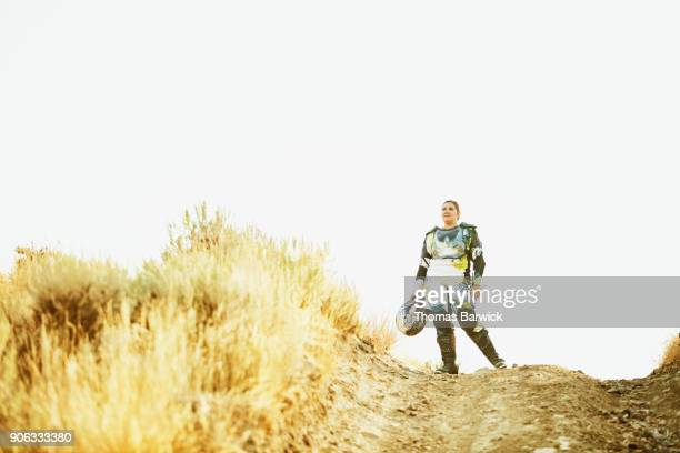 Female dirt bike rider standing at top of hill looking out after desert ride