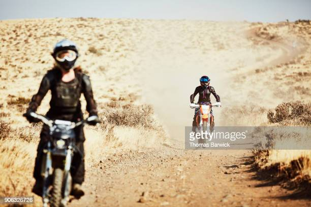 Female dirt bike riders on desert road on summer afternoon