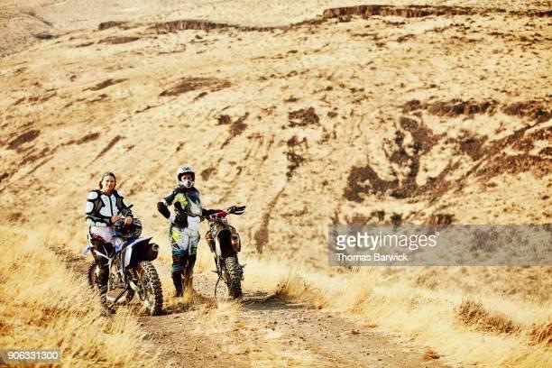 Female dirt bike riders resting during ride on desert road