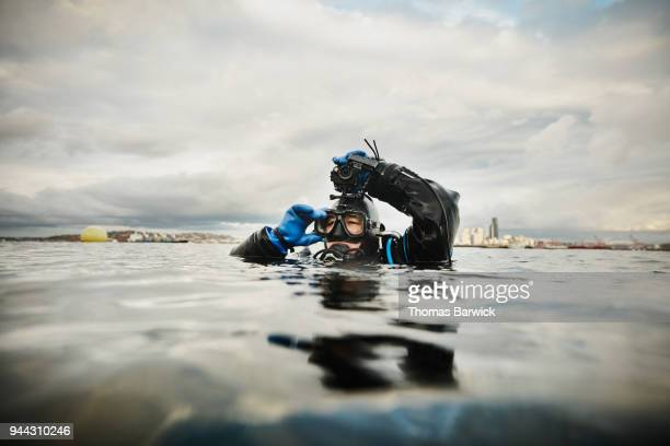 Female diver adjusting camera before descending on open water dive