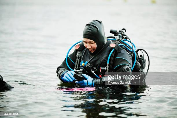 Female diver adjusting camera before open water dive