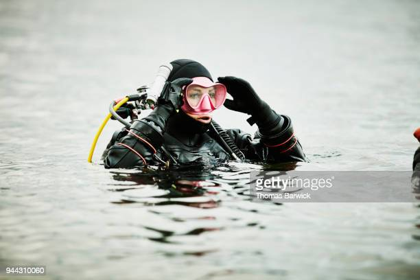 Female diver adjusting mask in water before open water dive