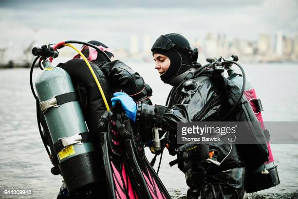 Female diver helping dive partner with fins before open water dive