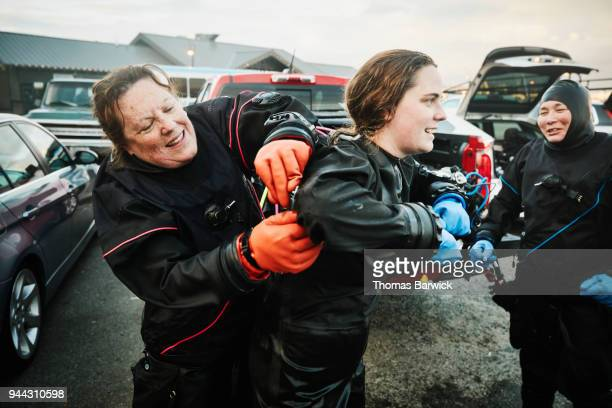 Female diver helping unzip dive partners drysuit after open water dive