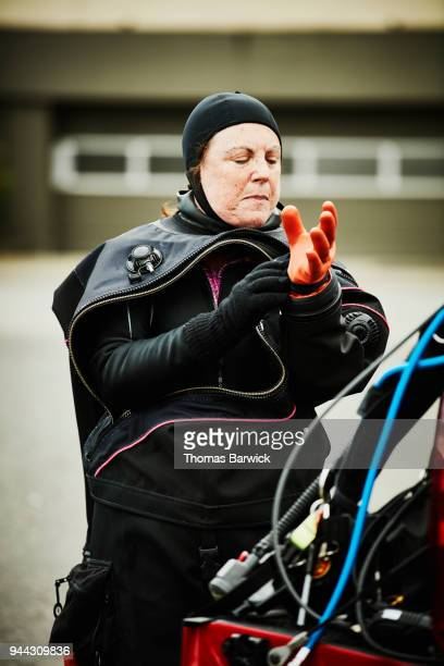 Female diver putting gloves on drysuit while preparing for open water dive