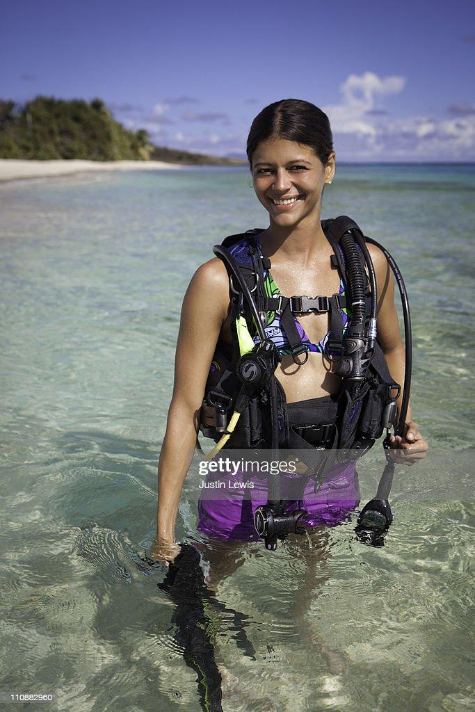 female diver with dive gear in tropical setting : Bildbanksbilder