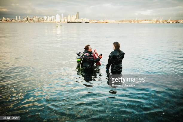 Female divers in discussion at shoreline after open water dive