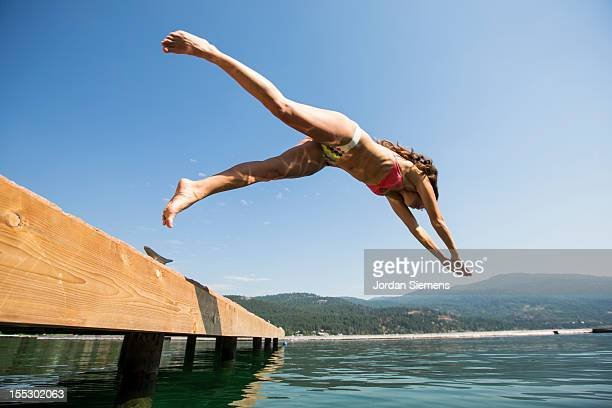 A female dives into the cool water of a lake.