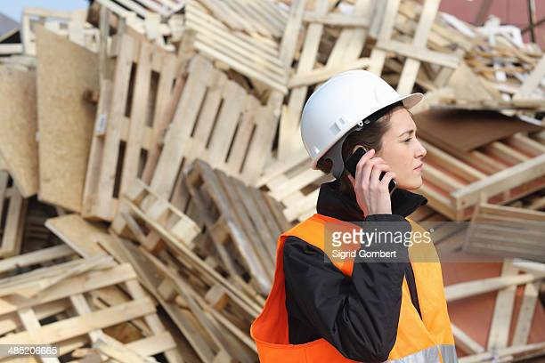 female dockworker using cellular phone - sigrid gombert stock-fotos und bilder