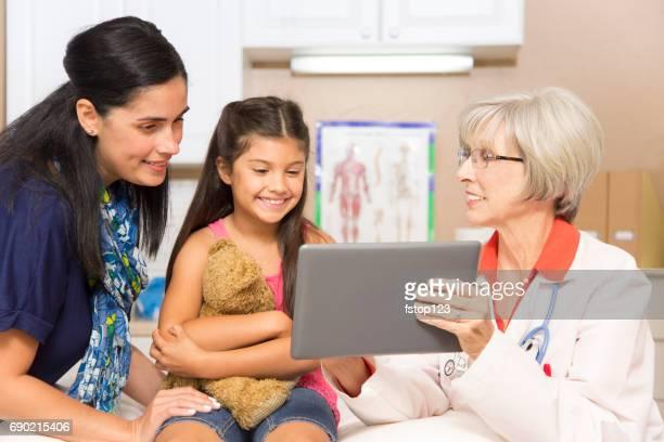Ärztin und lateinischen Abstammung Mädchen Patient im Büro oder in der Klinik der Kinderarzt.