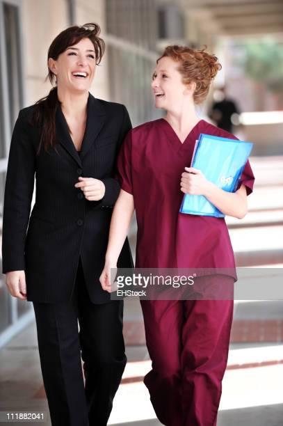 Ärztin und Krankenschwester Lachen im Krankenhaus-Korridor