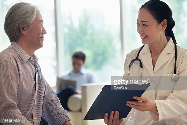 female doctor and patient sitting down and discussing medical record in the hospital - down blouse photos et images de collection
