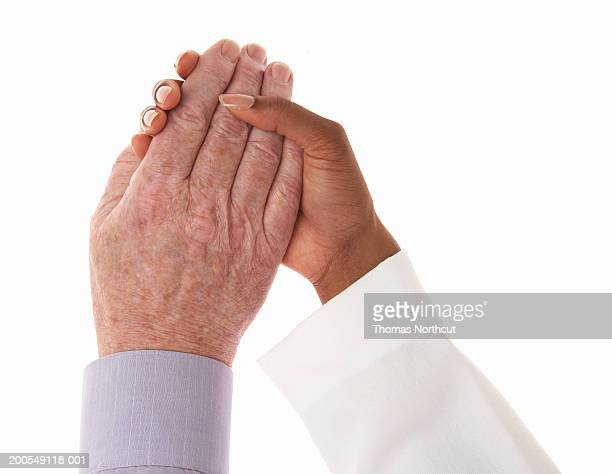 Female doctor and senior male patient holding hands, close-up of hands