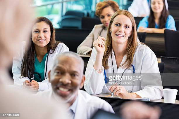 Female doctor asking question during healthcare seminar at hospital