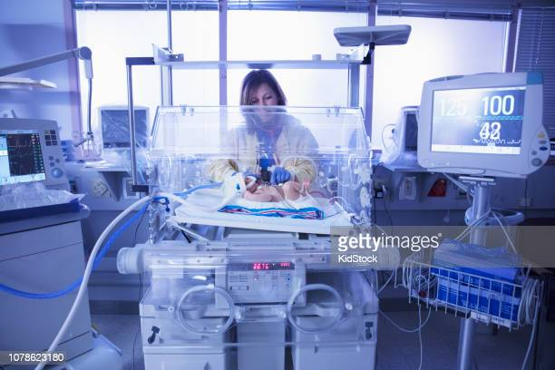 Female doctor assisting baby in intensive care unit