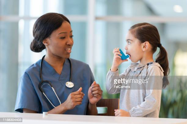 female doctor assists young asthmatic patient - respiratory system stock pictures, royalty-free photos & images