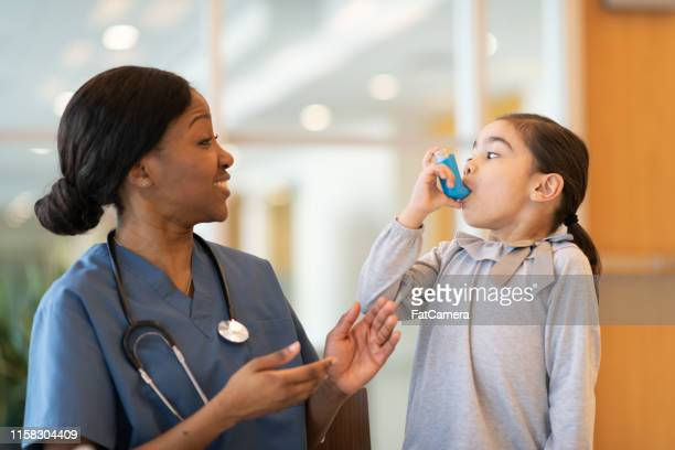 female doctor assists young asthmatic patient - asthma stock pictures, royalty-free photos & images