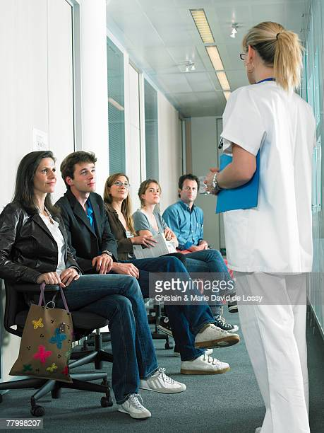Female doctor calling next patient in hospital waiting room.