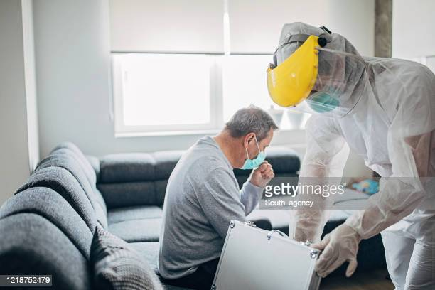 female doctor came to a senior man's house for covid-19 testing - helmet visor stock pictures, royalty-free photos & images