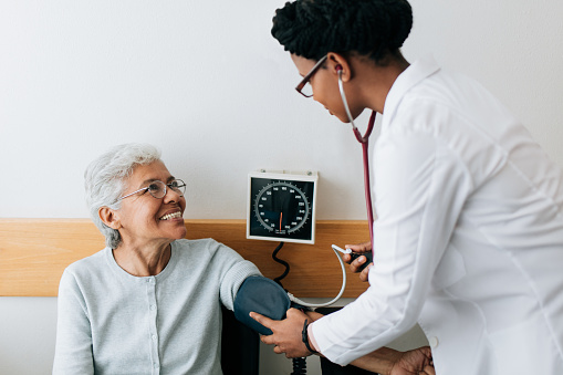 Female doctor checking blood pressure to senior patient 1094389100