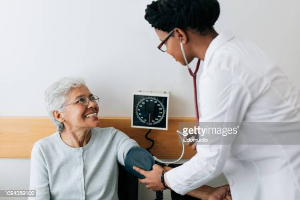 female doctor checking blood pressure to senior patient - blood pressure gauge stock pictures, royalty-free photos & images