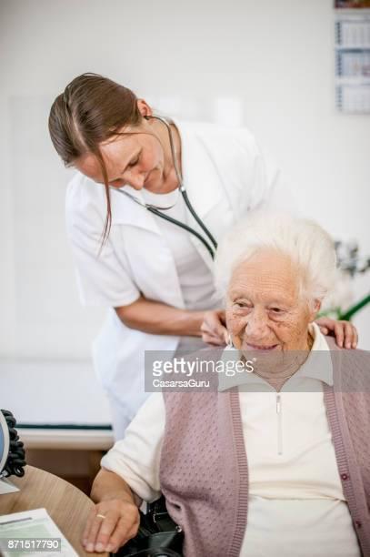 Doctora comprobación de glándulas de mujer Senior en hogar