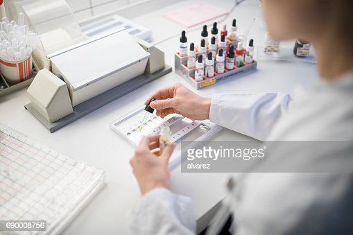 Female doctor collecting samples in tray at table