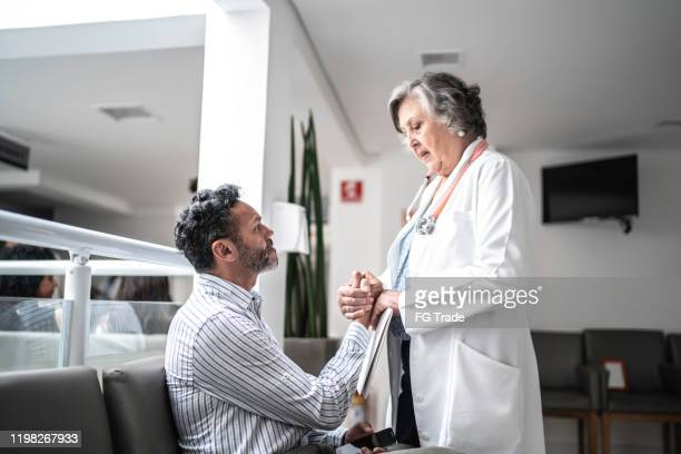 female doctor consoling sad man at hospital - suicide stock pictures, royalty-free photos & images