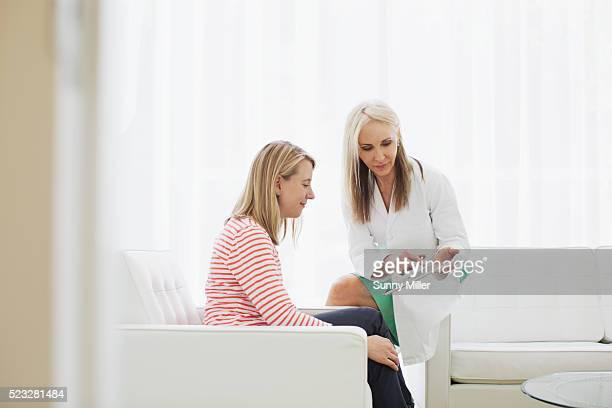 female doctor consulting patient - donne di età media foto e immagini stock