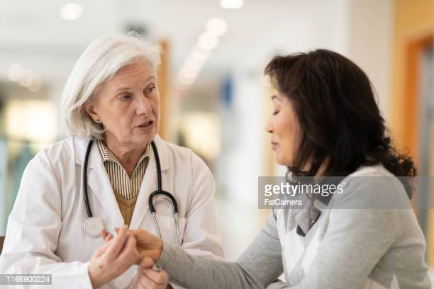 female doctor consults korean female patient - number 2 stock pictures, royalty-free photos & images
