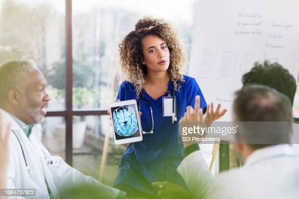 female doctor discusses brain x-ray during presentation - healthcare and medicine stock pictures, royalty-free photos & images