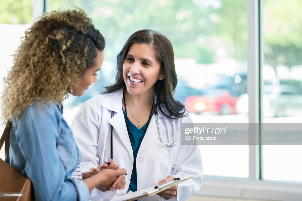 Female doctor discusses something with young mixed race patient : Stock Photo