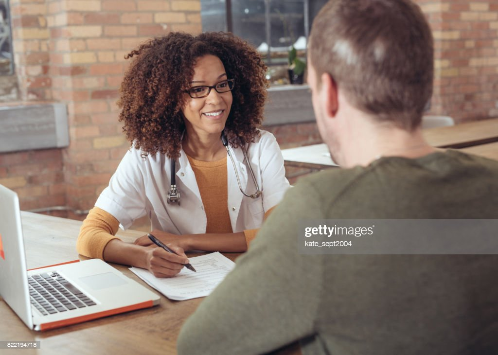 Female doctor discussing with a patient : Stock Photo