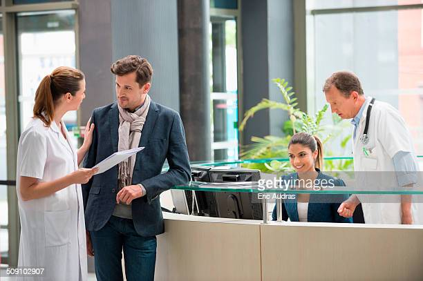 Female doctor discussing with patient at hospital reception desk