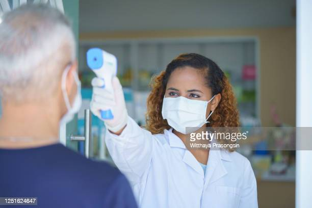 female doctor doing medical exam to a senior woman at her home - temperature checkpoint stock pictures, royalty-free photos & images