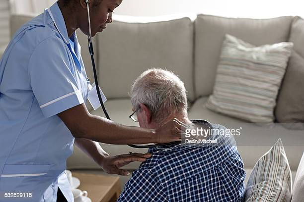 Female doctor doing medical examination of a senior man