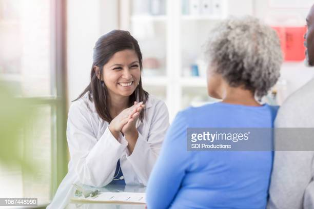 female doctor enjoys giving patients good news - good news stock pictures, royalty-free photos & images