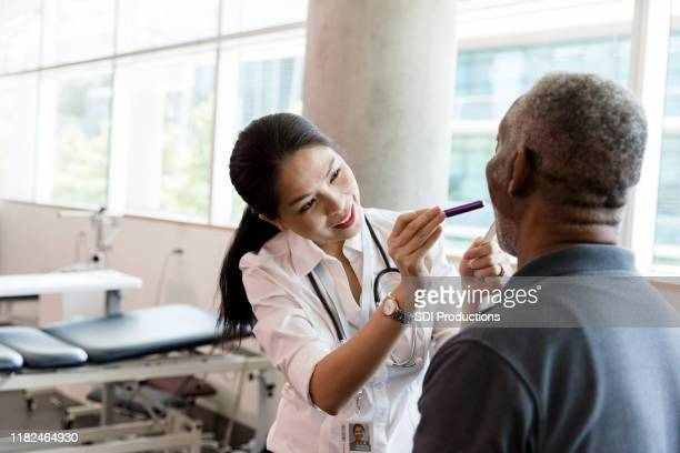 female doctor examines a senior man's throat - emergency medicine stock pictures, royalty-free photos & images