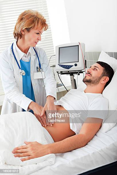 female doctor examining a young man - human stomach internal organ stock photos and pictures