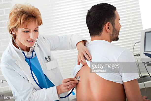 female doctor examining a young man - mycobacterium tuberculosis bacteria stock photos and pictures
