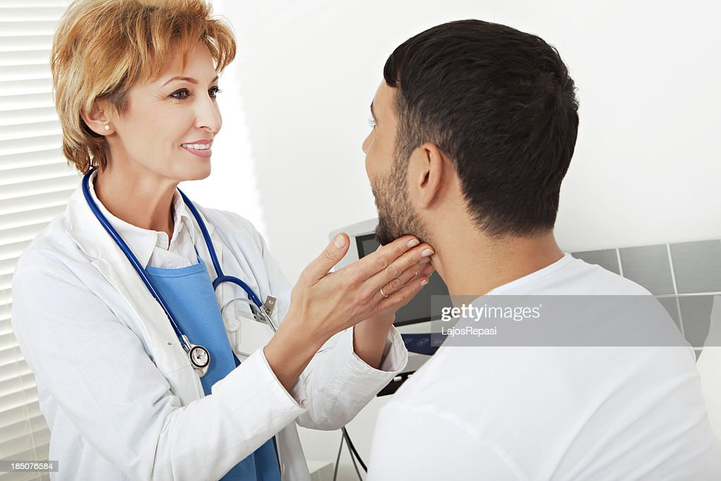 Female doctor examining a young man : Stock Photo