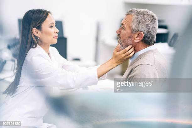 female doctor examining an older patient's throat - throat photos stock photos and pictures