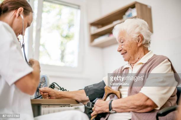 Female Doctor Examining Blood Pressure Of Senior Woman In Rest Home