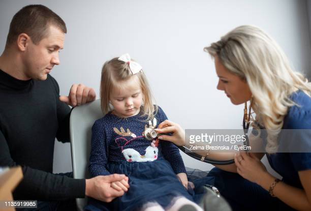 Female Doctor Examining Cute Girl Sitting By Father
