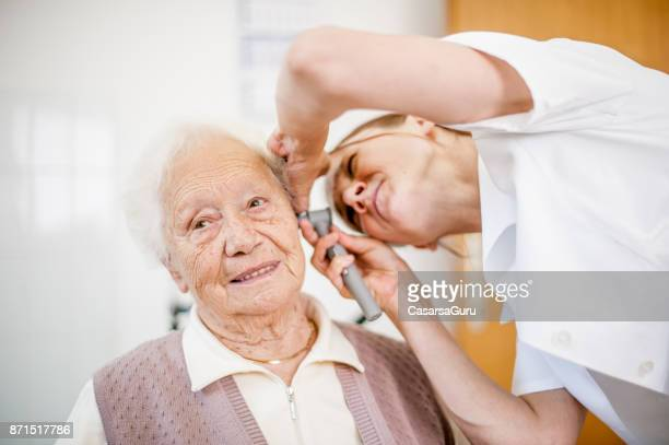 female doctor examining ear of senior woman in rest home - ear exam stock photos and pictures